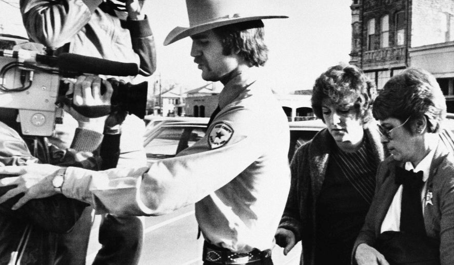 FILE - In this Feb. 16, 1984, file photo, Genene Jones, second right, is escorted into Williamson County Courthouse in Georgetown, Texas. Jones, a former nurse who's been serving a 99-year prison sentence since 1984 for the fatal overdose of an infant in her care, is due for early release in March 2018. A grand jury indicted her on Thursday, May 25, 2017, in the death of another infant as prosecutors try to keep her behind bars. (AP Photo/Ted Powers, File)