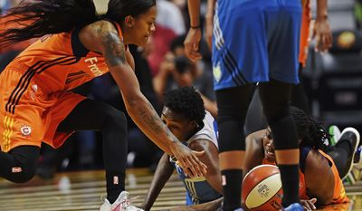Connecticut Sun's Courtney Williams, left, and Shekinna Stricklen, right, and Minnesota's Natasha Howard dive after the ball in the first half of a WNBA basketball game Friday, May 26, 2017, in Uncasville, Conn. (Sean D. Elliot/The Day via AP)