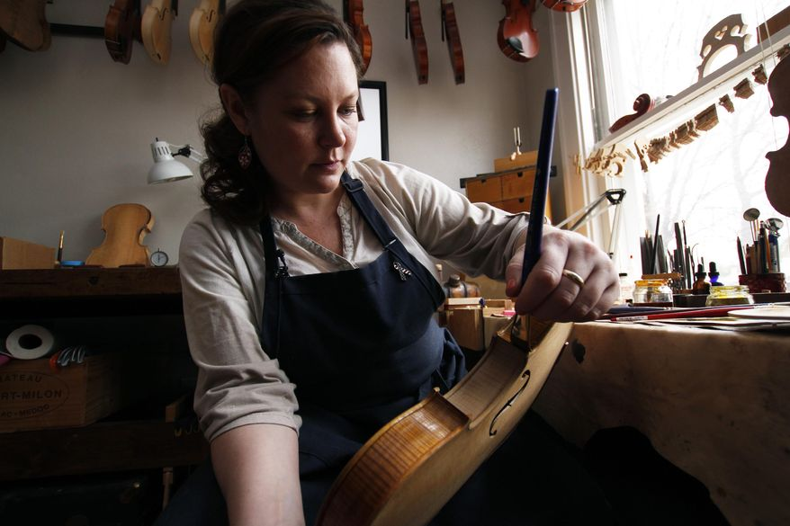 Sonja St. John applies varnish on a violin at her workshop in Neenah, Wis., on Thursday, April 27, 2017. Her brother, Jon St. John, died in Iraq in 2007 while serving in the military. Among other things, Sonja has found solace in her career, making and restoring violins. (AP Photo/Carrie Antlfinger)