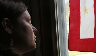 Sonja St. John sits in her Neenah, Wis., home on Monday, May 8, 2017, next to a window with a military service flag. The flag honors her brother, Jon St. John, who died in Iraq on Jan. 27, 2017, while serving in the Army. He was 25. Sonja, his only sibling, has struggled mightily since his death but has found solace in her career, making and restoring violins. She also recently played violin on a song for her brother. It was written from her journal entries with the help of a nonprofit arts project for veterans called Warrior Songs. (AP Photo/Martha Irvine)