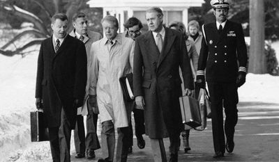 FILE - In this Feb. 14, 1979 file photo, President Jimmy Carter, flanked by Secretary of State Cyrus, right, and his advisor on foreign policy, Zbigniew Brzezinski, left, walk toward a waiting helicopter to fly to the nearby Andrews Air Force Base, Md. Brzezinski, the national security adviser to President Carter, has died at age 89. His death was announced on social media Friday night, May 26, 2017, by his daughter, MSNBC host Mika Brzezinski.  (AP Photo/Bob Daugherty, File)
