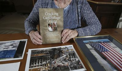 """In this Thursday, March 23, 2017 photo, U.S. Army Col. Janet Horton, a retired military chaplain of 28 years, poses for a photo with pictures of the Pentagon from the Sept. 11 terrorist attack and her book titled """"Cracking The Camouflage Ceiling"""" at her home in southeast Ocala, Fla. The terrorist plane struck the south side of the building where her office was, but she had been called away to get dental X-rays. Ironically, she was supposed to get them on August 11, her birthday, but the dental assistant had misplaced her file. (Bruce Ackerman/Star-Banner via AP)"""