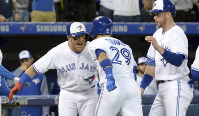 Toronto Blue Jays Troy Tulowitzki, left, and Justin Smoak, right, celebrate teammate Devon Travis' (29) grand slam against the Texas Rangers during second-inning baseball game action in Toronto, Friday, May 26, 2017. (Jon Blacker/The Canadian Press via AP)