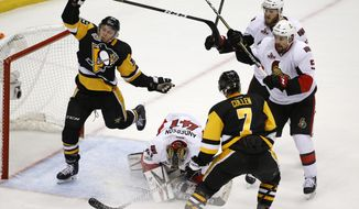 Ottawa Senators goalie Craig Anderson (41) blocks the puck as Pittsburgh Penguins' Jake Guentzel (59) and Kyle Turris (7) approach the goal against Ottawa Senators' Fredrik Claesson (33) and Cody Ceci (5) during overtime of Game 7 of the Eastern Conference final in the NHL Stanley Cup hockey playoffs in Pittsburgh, Thursday, May 25, 2017. (AP Photo/Gene J. Puskar)