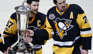 Pittsburgh Penguins' Sidney Crosby (87) and Evgeni Malkin (71) pose with the the Prince of Wales Trophy after beating the Ottawa Senators 3-2 in the second overtime period during Game 7 of the Eastern Conference final in the NHL Stanley Cup hockey playoffs in Pittsburgh, Thursday, May 25, 2017. (AP Photo/Gene J. Puskar)