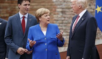 German Chancellor Angela Merkel, center, talks with Canadian Prime Minister Justin Trudeau, left, and President Donald Trump during a family photo with G7 leaders at the Ancient Greek Theater of Taormina during the G-7 summit, Friday, May 26, 2017, in Taormina, Italy. (AP Photo/Evan Vucci) ** FILE **
