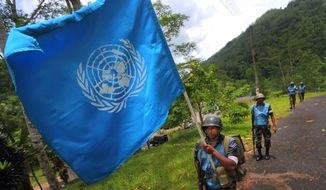 In this Sept. 13, 2016 photo, a Sri Lanka Air Force airman carries the U.N. flag during training for a road patrol at the Institute of Peace Support Operations Training in Kukuleganga, Sri Lanka. Instructors at the training camp said they have taken steps to address the risk of sexual abuse and exploitation since the child sex ring scandal in Haiti. (AP Photo/Eranga Jayawardena)