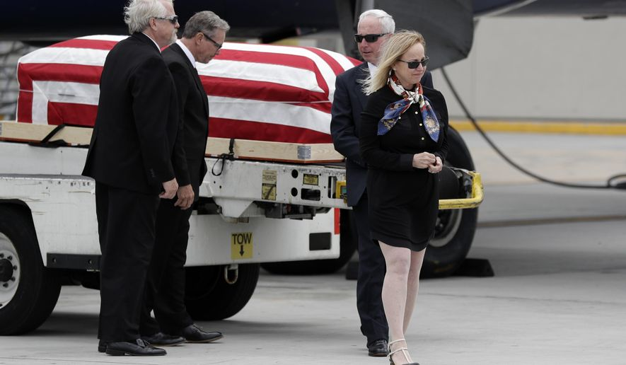 Deborah Crosby, right, walks away from her father's casket after its arrival to the airport Friday, May 26, 2017, in San Diego. Her brothers, Douglas Crosby, left, John Crosby, second from left, and Steven Crosby look on. After spending more than half a century on getting her father's remains recovered from Vietnam after his Navy plane was shot down there in 1965, Crosby watched Friday as his casket was removed from a Delta Air Lines jet at San Diego's airport and six sailors transferred it to a hearse. (AP Photo/Gregory Bull)