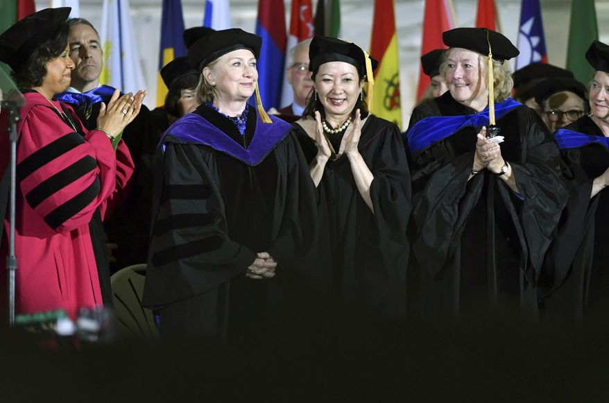 Faculty members cheer former Secretary of State Hillary Clinton after she delivered the commencement address at Wellesley College, Friday, May 26, 2017 in Wellesley, Mass. Clinton graduated from the school in 1969. (AP Photo/Josh Reynolds)