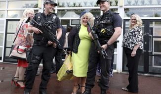 Racegoers interact with armed police inside Haydock Park Racecourse in Haydock, England, Saturday, May 27, 2017. British police are preparing major security operations as people across Britain begin celebrating a three-day holiday weekend. Five days after a bomber killed more than 20 people at a concert in Manchester, more than a thousand armed police are on standby as major events including the Football Association Cup Final and the Premiership Rugby Final are expected to draw tens of thousands of people. (Martin Rickett/PA via AP)