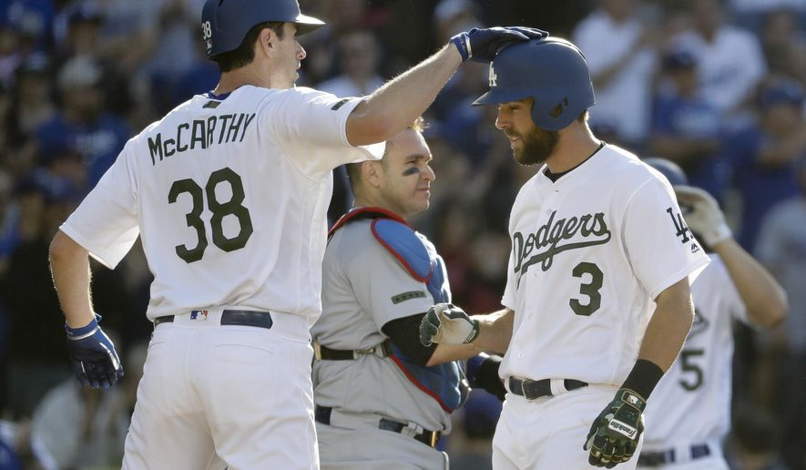 Los Angeles Dodgers' Chris Taylor, right, celebrates his two-run home run with Brandon McCarthy as Chicago Cubs catcher Miguel Montero looks on during the fifth inning of a baseball game in Los Angeles, Saturday, May 27, 2017. (AP Photo/Chris Carlson)