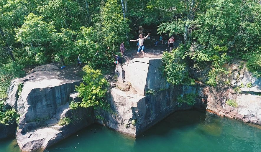 "This June 10, 2016, photo provided by drone filmmaker Spencer Kuhlman shows a photograph made by Kuhlman using a drone above a popular cliff jumping and diving spot near St. Cloud, Minn. Kuhlman is a finalist in the first-ever Fargo, N.D., drone film festival, which will announce its winners next week. His piece called ""Across The World"" includes several action shots like the one shown in the photo. (Spencer Kuhlman via AP)"