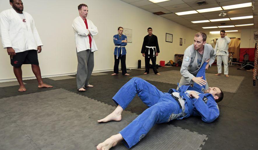 ADVANCE FOR WEEKEND EDITIONS - In this May 17, 2017, photo, jiujitsu instructor Shane McFarland, in grey, uses student Turner McCulley, in blue, to demonstrate a throw during a class at his studio in Pullman, Wash. McFarland has found himself somewhere he never expected - a Peace Corps alum working toward his doctorate and a Brazilian jiujitsu instructor with his own martial arts studio. (Kai Eiselein/The Moscow-Pullman Daily News via AP)