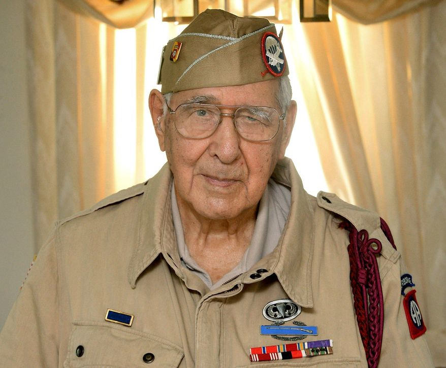 In this May 18, 2017, photo, Joseph Morettini, 92, center, of Erie, Pa., poses for a photo. In the early morning hours of D-Day, June 6, 1944,  Morettini, a 19-year-old paratrooper with the U.S. Army 82nd Airborne Division, jumped from a Douglas C-47 Skytrain over France's Normandy coast. (Jack Hanrahan/Erie Times-News via AP)