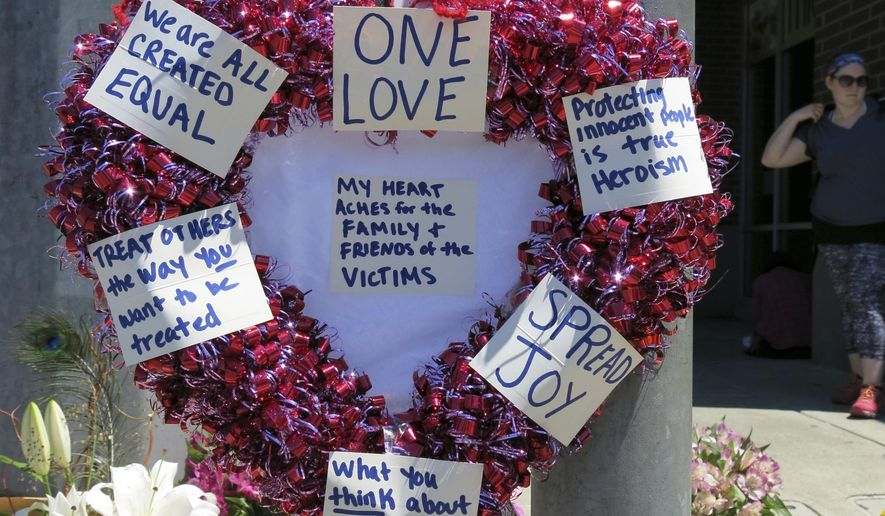A heart-shaped wreath covered with positive messages hangs on a traffic light pole at a memorial for two bystanders who were stabbed to death Friday, while trying to stop a man who was yelling anti-Muslim slurs and acting aggressively toward two young women, including one wearing a Muslim head covering, on a light-trail train in Portland, Ore, Saturday, May 27, 2017. A memorial grew all day Saturday outside the transit center in Portland, as people stopped with flowers, candles, signs and painted rocks. Jeremy Joseph Christian, 35, was booked on suspicion of murder and attempted murder in the attack. (AP Photo/Gillian Flaccus)