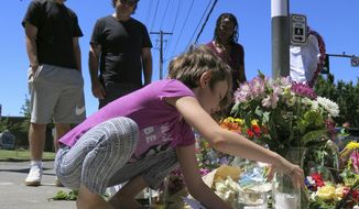 Coco Douglas, 8, leaves a handmade sign and rocks she painted at a memorial in Portland, Ore., on Saturday, May 27, 2017, for two bystanders who were stabbed to death Friday while trying to stop a man who was yelling anti-Muslim slurs and acting aggressively toward two young women. From left are Coco's brother, Desmond Douglas; her father, Christopher Douglas; and her stepmother, Angel Sauls. (AP Photos/Gillian Flaccus)