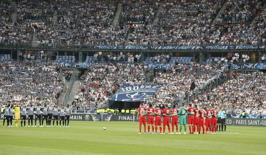 Paris Saint Germain and Angers players pause for a minute's silence, as a tribute to the victims of the Manchester bomb attack, before the French Cup 2017 Final soccer match, between Paris Saint-Germain (PSG) and Angers at Stade de France in Saint Denis, north of Paris, France, Saturday, May 27, 2017. (AP Photo/Francois Mori)