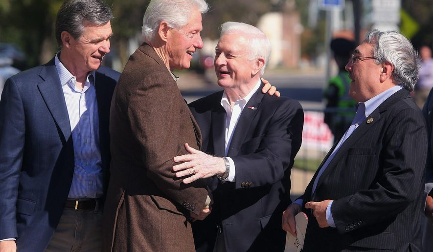FILE- This Oct, 25, 2016 file photo shows former President Bill Clinton, second from left, greets former North Carolina Gov. Jim Hunt, second from right, U.S. Rep. G.K. Butterfield, D-1st District, right, and then North Carolina Attorney General Roy Cooper during a rally, while campaigning for Democratic presidential nominee Hillary Clinton. The four-term Democratic governor is among the state's most influential politicians of the 20th century, but remains engaged in 21st century policy and politics as he turned 80 years old in May. (Alan Campbell/The Rocky Mount Telegram via AP, File)