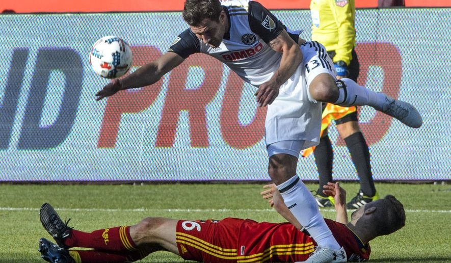 Real Salt Lake defender Chris Wingert (16) falls to the gourd as Philadelphia Union forward Chris Pontius (13) tries to control the ball in an MLS soccer match in Sandy, Utah, Saturday, May 27, 2017. (Steve Griffin/The Salt Lake Tribune via AP)