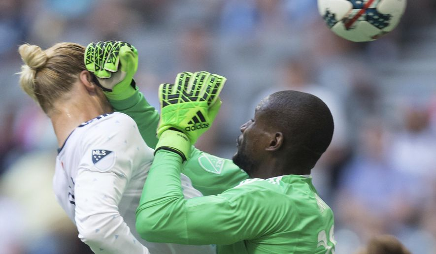 D.C. United goalkeeper Bill Hamid, right, strikes Vancouver Whitecaps' Brek Shea in the face, resulting in a penalty kick, during the second half of an MLS soccer game in Vancouver, British Columbia, Saturday, May 27, 2017. (Darryl Dyck/The Canadian Press via AP)