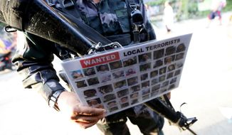 "A police officer holds a poster of wanted Filipino Muslim militants known as ""Maute "" group at a checkpoint set up at the entrance to Iligan city Saturday, May 27, 2017 in southern Philippines. Iligan city is one of the safe havens for the tens of thousands of Marawi residents who have fled their city following the rampage by Muslim militants. (AP Photo/Bullit Marquez)"