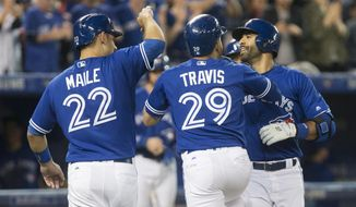 Toronto Blue Jays' Jose Bautista, right, celebrates with teammates Devon Travis (29) and catcher Luke Maile (22) after hitting a three-run home run against the Texas Rangers during the fifth inning of a baseball game in Toronto on Saturday, May 27, 2017. (Chris Young/The Canadian Press via AP)
