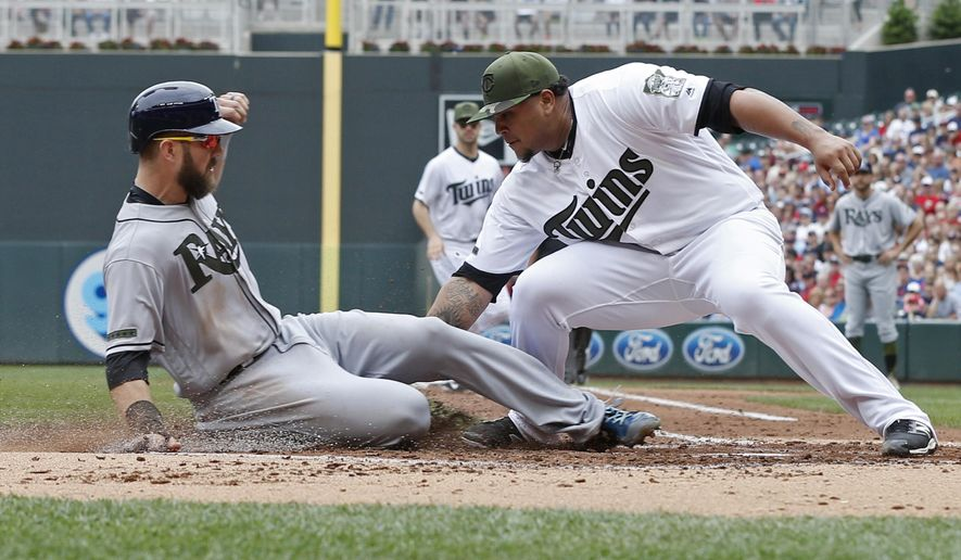 Minnesota Twins pitcher Adalberto Mejia, right, makes the tag at the plate on Tampa Bay Rays' Steven Souza Jr. who attempted to score on a runner's fielders' choice in the second inning of a baseball game Saturday, May 27, 2017, in Minneapolis. AP Photo/Jim Mone)
