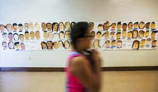 In this May 9, 2017, photo a poster of self-portraits hand painted by students is displayed in a hallway at Hoover Elementary School in Yakima, Wash. (Shawn Gust/Yakima Herald-Republic via AP)