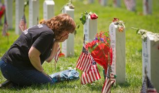 Karen Clarkson, of Fairbanks, Alaska, kneels and cries at the grave of her son U.S. Army Sergeant Joel Clarkson on Memorial Day at Arlington National Cemetery in Arlington, Va., Monday, May 28, 2012. (Rod Lamkey Jr/The Washington Times)