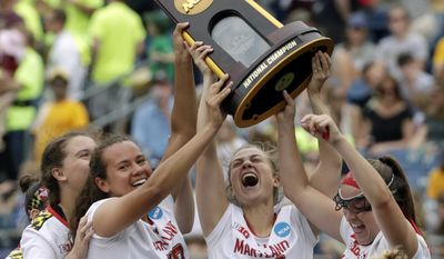 Maryland's Alex McKay (19), Bairre Reilly (32) and Meghan Doherty, far right, celebrate with the trophy after they defeated Boston College to win the NCAA college Division 1 lacrosse championship final, Sunday, May 28, 2017, in Foxborough, Mass. (AP Photo/Elise Amendola)