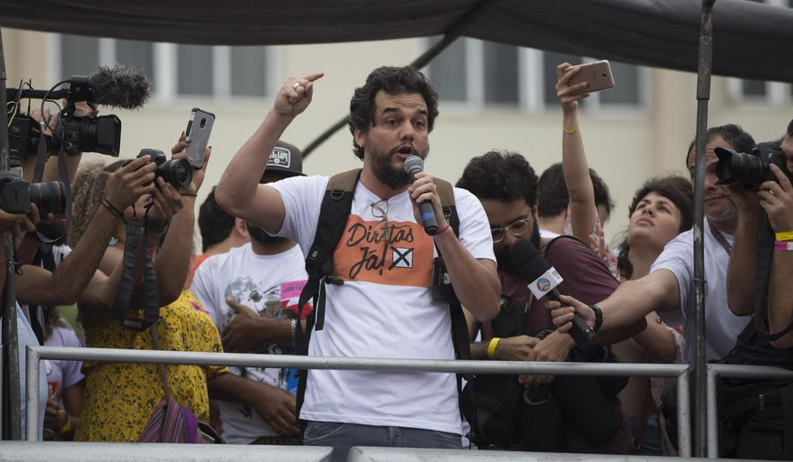 "Brazilian actor Wagner Moura, wearing a T-shirt that reads in Portuguese ""Elections now"" speaks during a protest against Brazil's president Michel Temer at Copacabana beach in Rio de Janeiro, Brazil, Sunday, May 28, 2017. People gathered on Copacabana beach ahead of a concert by Brazilian musical performers calling for new presidential elections while pressure mounts on the country's leader to resign amid corruption allegations. (AP Photo/Leo Correa)"
