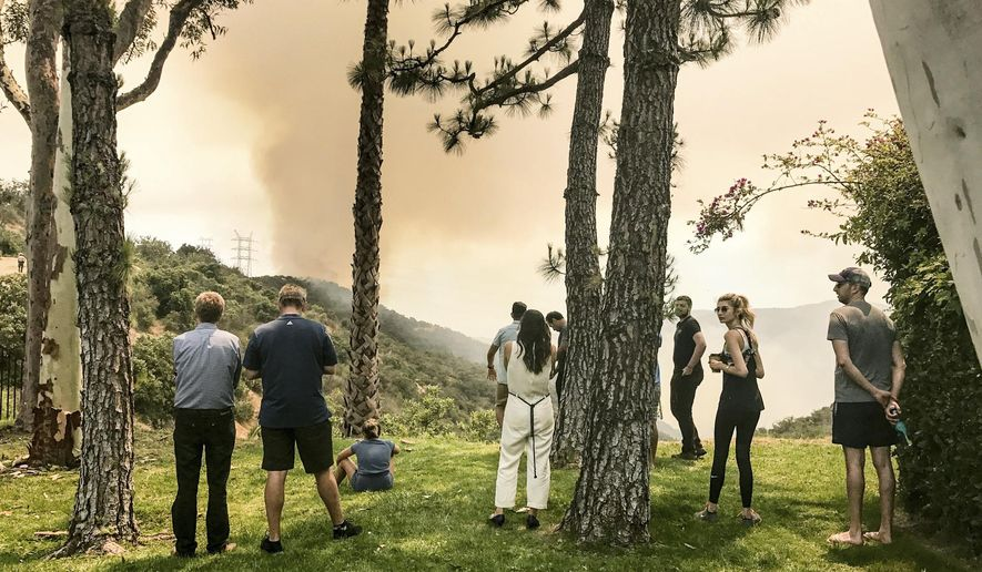 Mountaingate Residents watch a wildfire near their home in Brentwood, Calif., Sunday, May 28. 2017. Ground crews getting help from water-dropping aircraft are battling two brush fires in Los Angeles. A small blaze Sunday near large homes in the Mandeville Canyon area above Brentwood is sending up a huge plume of smoke visible for miles. (David Crane/Los Angeles Daily News via AP)