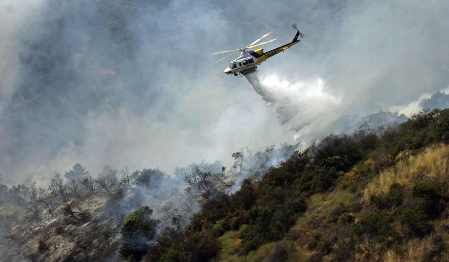 A helicopter makes a water drop on a hillside after a wildfire broke out in the Brentwood area of Los Angeles, Sunday, May 28, 2017. A dark plume of smoke was visible for miles as the fire consumed moderate to thick brush near Mandeville Canyon Road, a dead end road that snakes up a deep canyon lined by expensive view homes. A few residents voluntarily left but no homes were damaged. (AP Photo/Brian Melley)