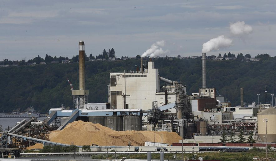 FILE - In this June 1, 2016, file photo, piles of wood chips sit near the RockTenn paper mill in Tacoma, Wash. Even as the Trump administration seeks to roll back Obama-era rules to curb greenhouse gas emissions at coal-fired power plants, Washington state is forging ahead with its own rules to cap carbon pollution from big industrial facilities. But the state faces legal challenges as it begins requiring large polluters such as RockTenn. (AP Photo/Ted S. Warren, File)