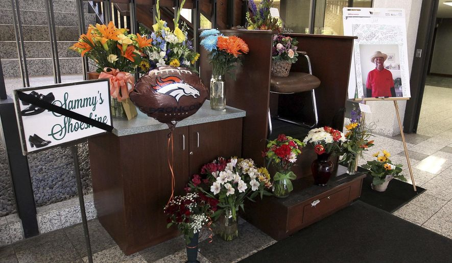 In this May 22, 2017 photo, bouquets of flowers, a balloon and a large photo of Sammy Hudson signed by dozens of well-wishers decorate Sammy's Shoeshine in the lobby of the Alpine Bank building,  in Grand Junction, Colo. Hudson ran the shoeshine business for decades until he died on May 19. (Gretel Daugherty /The Grand Junction Daily Sentinel via AP)