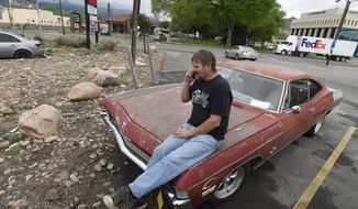 In this May 10, 2017, photo, Rick Ratzlaff talks on the phone while sitting on his vintage car in Canon City, Colo. Ratzlaff said he was surprised to find murder evidence from the cold case of a murdered teen inside the unit, which was rented by Lt. Robert Dodd with the Fremont County Sheriff's Office. The contents were put up for auction after Dodd failed to make the payments on the unit. (Jerilee Bennett/The Gazette via AP)