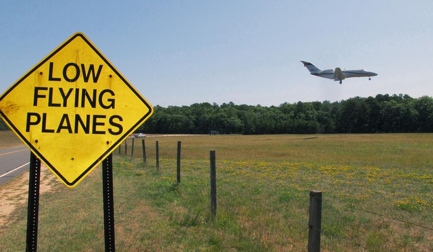 FILE - In this Aug. 20, 2014, file photo, a small jet approaches the runway at East Hampton Town Airport in East Hampton, N.Y. East Hampton officials enacted curfews and limits on the frequency of flights to quiet the skies above the resort towns for the haves and have-mores. But an appeals court struck down those laws last winter and now the town, with the support of New York City and others arguing for local control of airports, are asking he U.S. Supreme Court to intervene. (AP Photo/Frank Eltman, File)