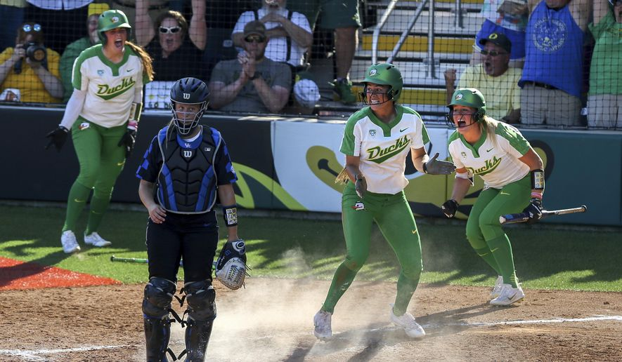 Oregon's Nikki Udria, second from right, scores on a Mia Camuso base hit double-RBI in the seventh inning as Gwen Svekis, left, and Miranda Elish celebrate during their win over Kentucky in the NCAA college softball super regionals on Saturday, May 27, 2017, in Eugene, Ore. (Collin Andrew/The Register-Guard via AP)