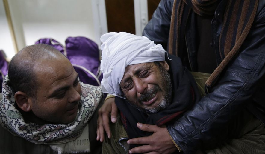 In this Monday, Feb. 16, 2015, file photo, a man is comforted by others as he mourns over Egyptian Coptic Christians who were captured in Libya and killed by militants affiliated with the Islamic State group, outside of the Virgin Mary church in the village of el-Aour, near Minya, 220 kilometers (135 miles) south of Cairo, Egypt. (AP Photo/Hassan Ammar, File)