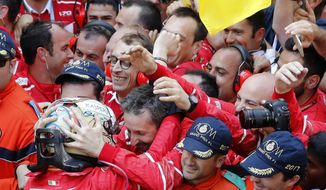 Ferrari driver Sebastian Vettel of Germany, left, celebrates after winning the Formula One Grand Prix at the Monaco racetrack in Monaco, Sunday, May 28, 2017. (AP Photo/Frank Augstein)
