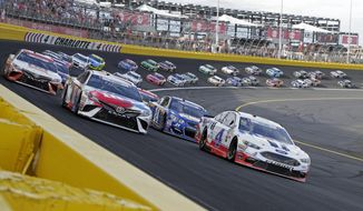 Kevin Harvick (4) and Kyle Busch (18) lead the field for the start of the NASCAR Cup series auto race at Charlotte Motor Speedway in Concord, N.C., Sunday, May 28, 2017. (AP Photo/Chuck Burton)  **FILE**