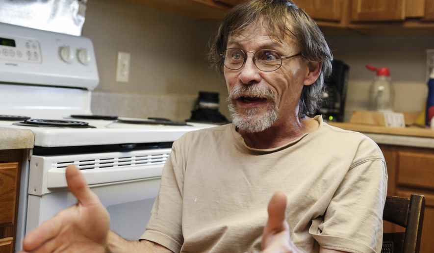 In this May 25, 2017 photo, Glenn Sharp, who sat out fines in jail, gestures in his Lincoln, Neb., apartment. Nebraska's largest county corrections departments spend millions each year incarcerating people who couldn't pay routine fines or afford bail, sometimes for nonviolent misdemeanors that wouldn't result in jail time. Advocates are optimistic that a law passed this session requiring judges to consider whether someone can afford a fine or bail before assigning it will keep more poor people out of jail. (AP Photo/Nati Harnik)