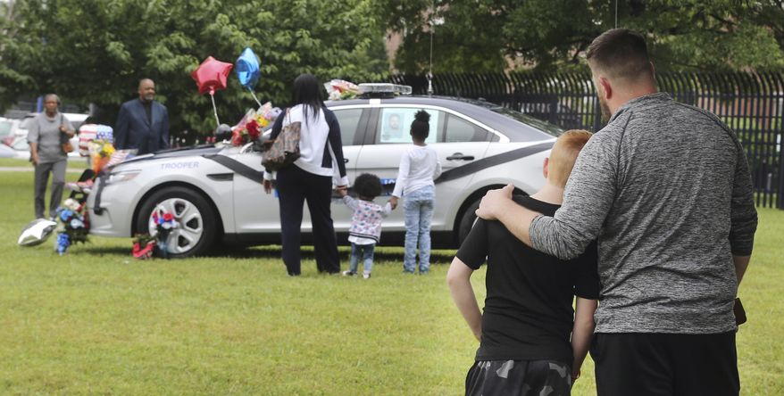 Brayden Dunning, 11, of Powhatan, Va., is comforted by his father, Brad Dunning, as they look at a police cruiser that stands outside the State Police of Virginia headquarters in Richmond, Va., on Sunday, May 28, 2017, as a memorial to Special Agent Michael T. Walter who died Saturday after being shot in a public housing project in Richmond Friday evening. (Joe Mahoney)/Richmond Times-Dispatch via AP)