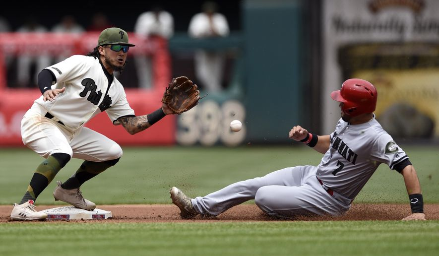 Cincinnati Reds' Eugenio Suarez (7) is caught stealing second base by Philadelphia Phillies' shortstop Freddy Galvis during the first inning of a baseball game on Sunday, May 28, 2017, in Philadelphia. (AP Photo/Michael Perez)