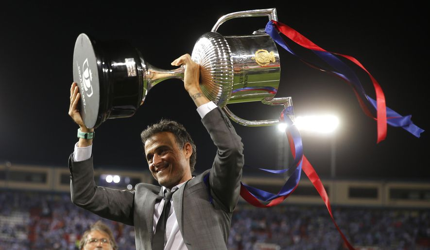 Barcelona's head coach Luis Enrique holds up the cup after winning the Copa del Rey final soccer match between Barcelona and Alaves at the Vicente Calderon stadium in Madrid, Spain, Saturday May 27, 2017. (AP Photo/Daniel Ochoa de Olza)
