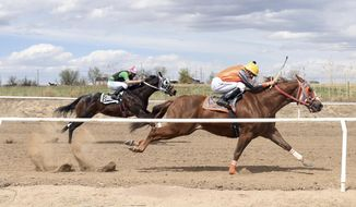 In this undated photo horses sprint by a small fence during the annual horse race at Rancho El Caporal near Fort Lupton, Colo. After race organizers provide the necessary documents to get a permit, there's little to no oversight, both from local law enforcement or state officials, something insiders and advocates say paves the way for illegal gambling, mistreatment of horses and a potentially unsafe environment for spectators. (Joshua Polson/The Greeley Tribune via AP)