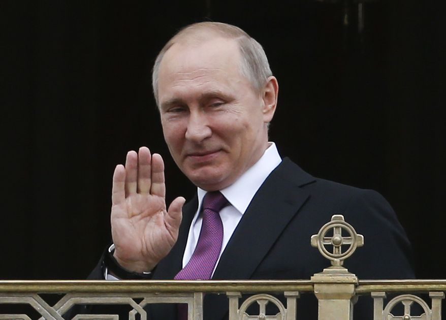 Russian President Vladimir Putin greets believers and participants as he visits the Sretensky Monastery to take part in a ceremony consecrating a new temple in Moscow, in this May 25, 2017, file photo. Putin is  visiting France on Monday, May 29, 2017, in hope of mending strained ties. (Sergei Karpukhin/Pool Photo via AP, File)