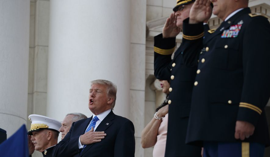 President Donald Trump sings the National Anthem during a Memorial Day ceremony at Arlington National Cemetery, Monday, May 29, 2017, in Arlington, Va. (AP Photo/Evan Vucci)