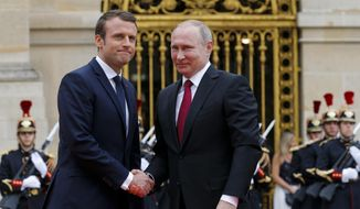 Russian President Vladimir Putin, right, is welcomed by French President Emmanuel Macron at the Palace of Versailles, near Paris, France, Monday, May 29, 2017. (AP Photo/Alexander Zemlianichenko, pool) ** FILE **