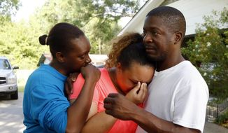 Christianna May-Kelly, center, is supported by family members as she cries after answering reporters questions outside her parents' home in Brookhaven, Miss., Sunday, May 28, 2017. May-Kelly said her mother was among the people gunned down during a shooting in rural Mississippi Saturday night. (AP Photo/Rogelio V. Solis)